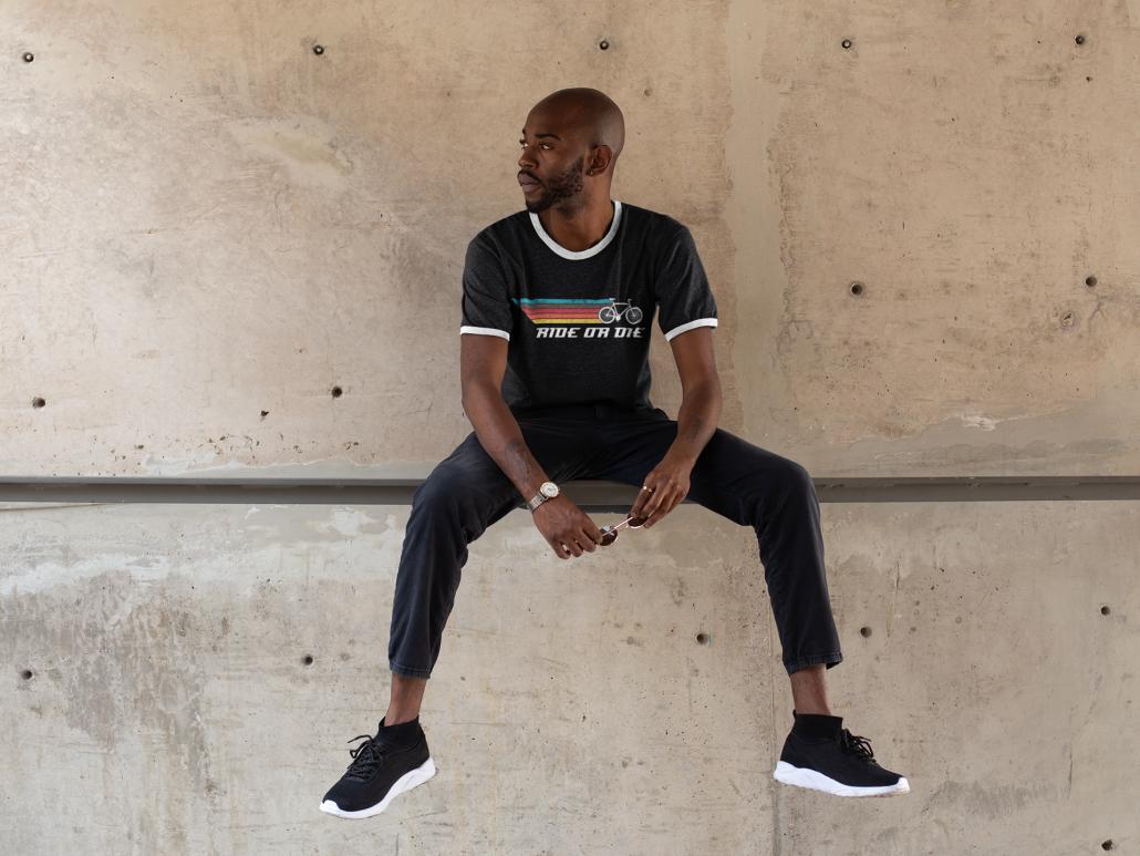 Mann sitzt auf einer Mauer und trägt ein sportliches T-Shirt mit Design