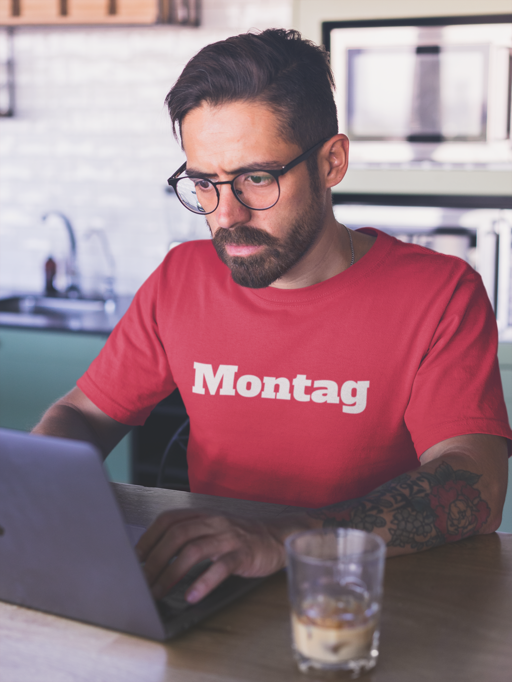 Mann arbeitet mit Montag T-Shirt am Rechner.