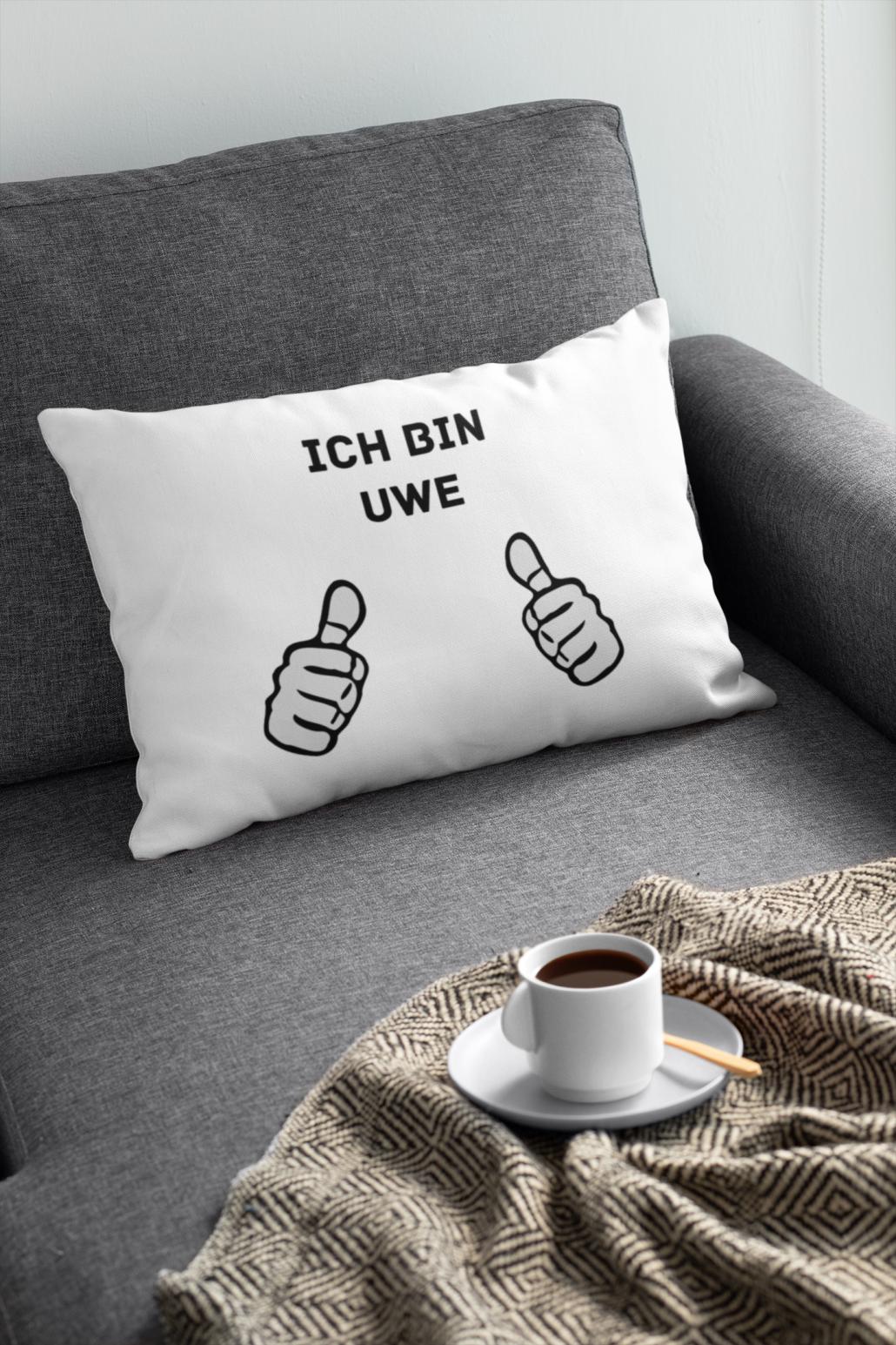 """Sofakissen auf Couch mit Aufdruck """"Ich bin Uwe"""" und zwei aufgedruckten Daumen, die auf Schriftzug zeigen, vor dem Kissen steht eine Kaffeetasse."""