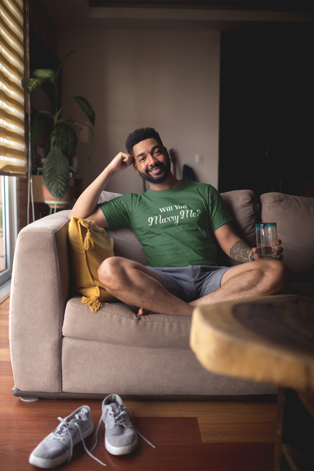 man wearing personalized t-shirt and sitting on a couch