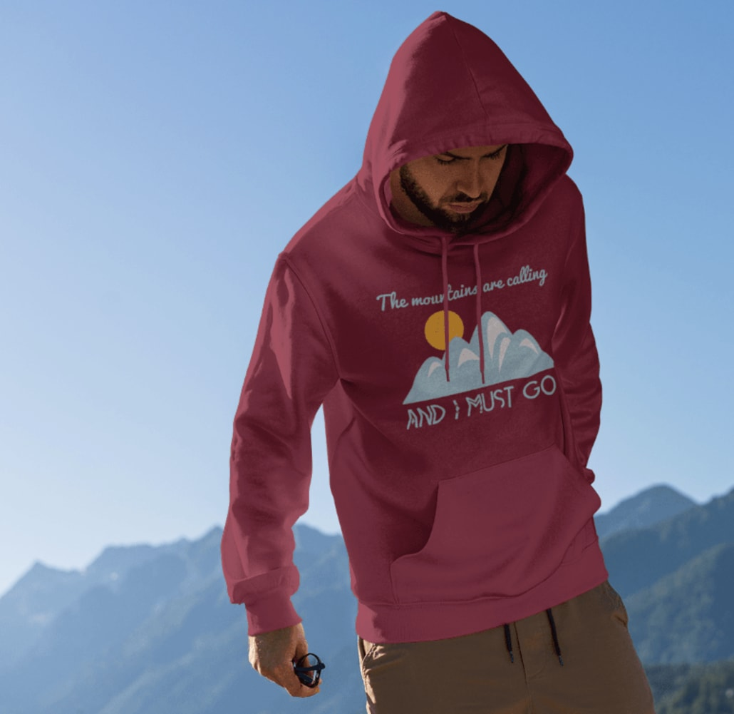 a man wearing a hoodie with mountains in the background