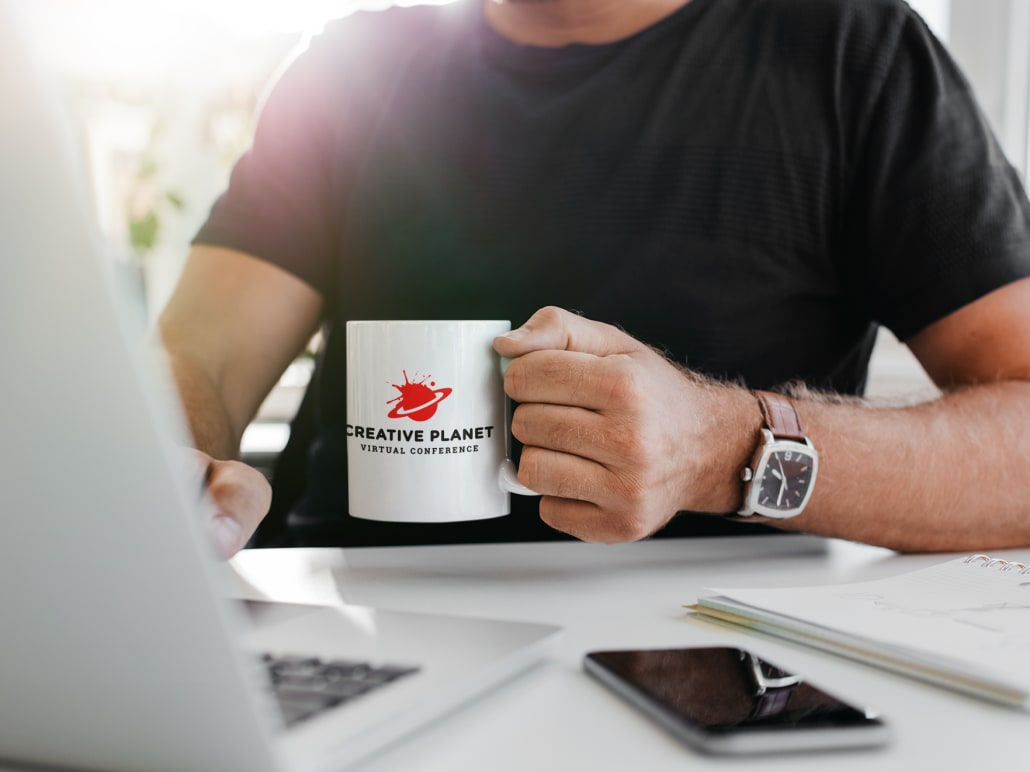 Guy with a coffe mug with conference logo