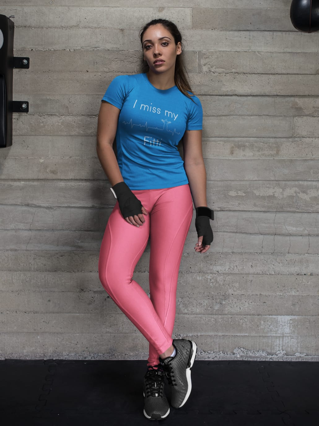 Junge Frau in Fitnessstudio mit pinkem Top und blauen Leggings