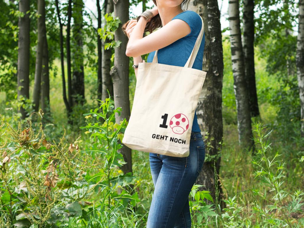 #Junge Frau im Wald trägt Stoffbeutel mit Aufdruck