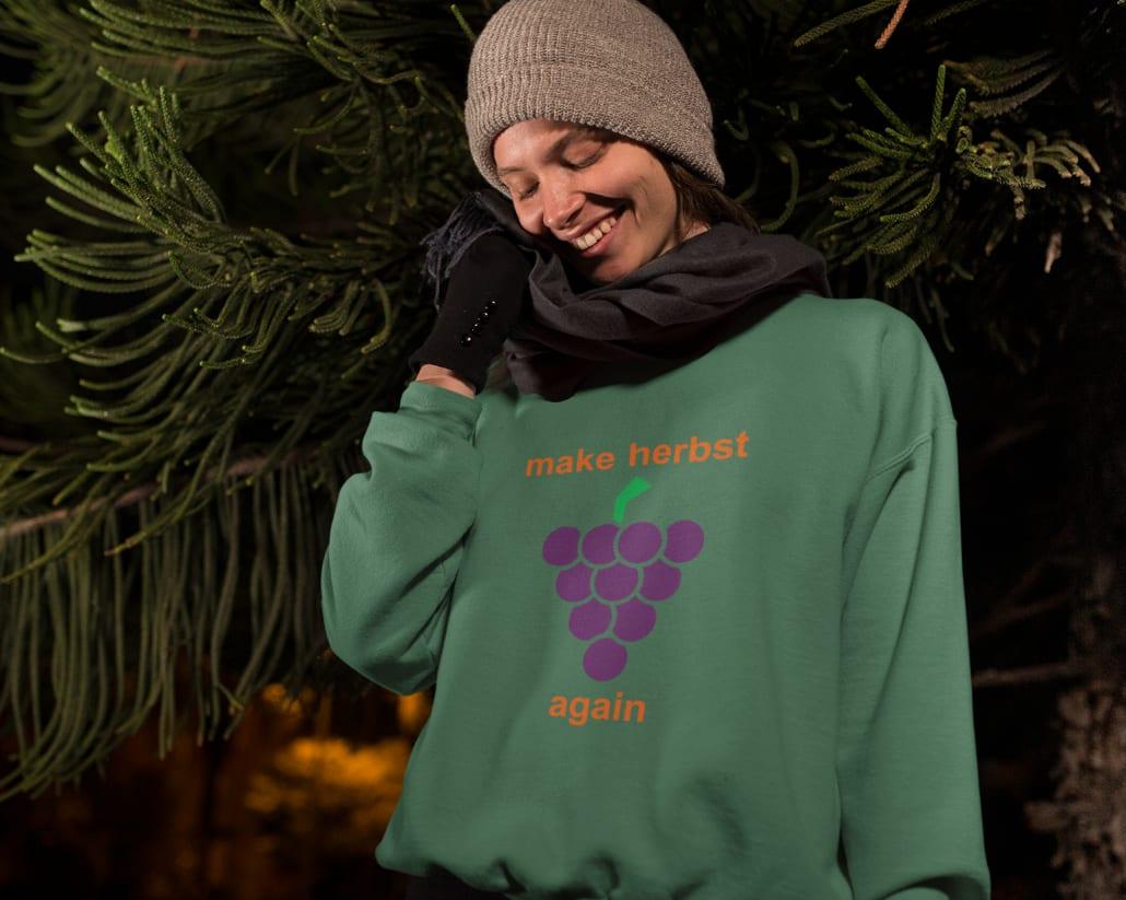 #Junge Frau mit Mütze, Schal und Handschuhen vor Baum stehend in einem grünen Sweater mit dem Aufdruck