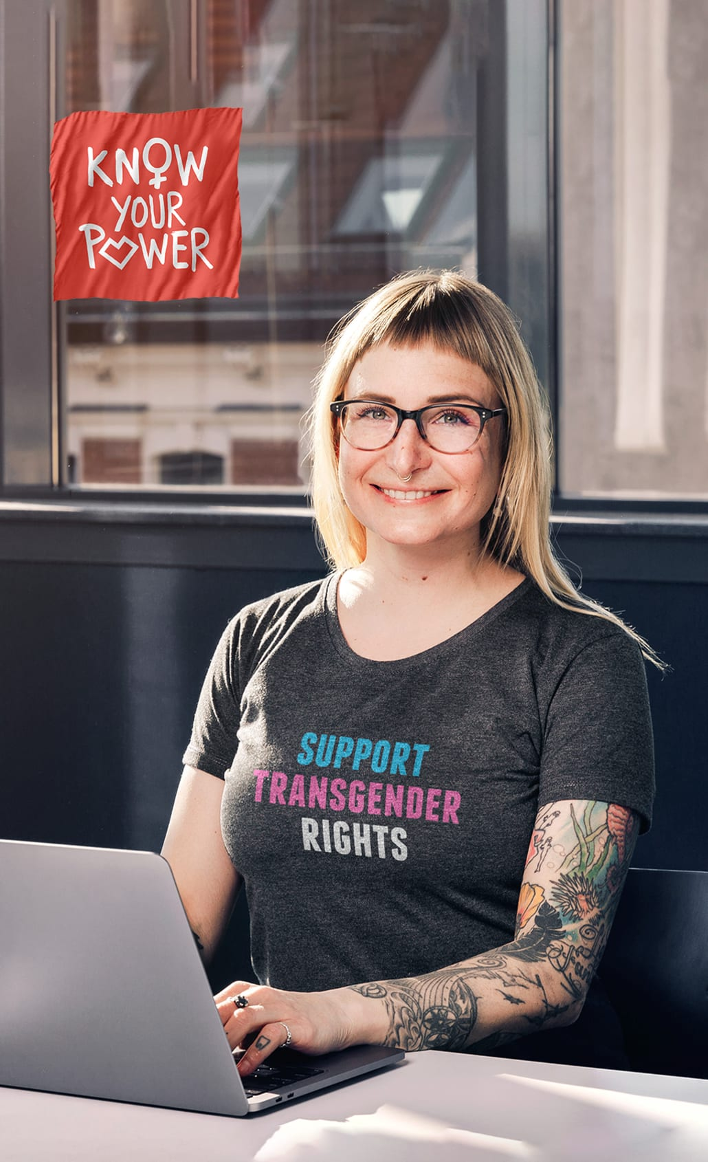 Sanja sitting at computer in gray t-shirt with motive: support transgender rights