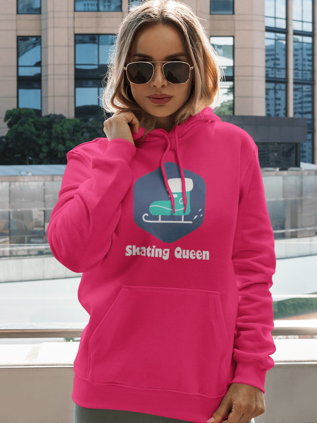 woman with a bitch pullover hoodie posing by a tall building