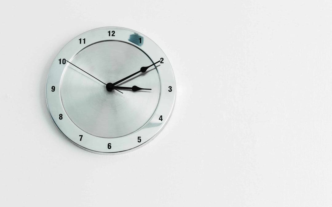 Silver, analog wall clock on a white wall.