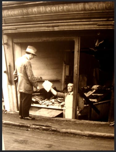 A butcher's shop serves a customer from below ground level. Photo from Stubby43