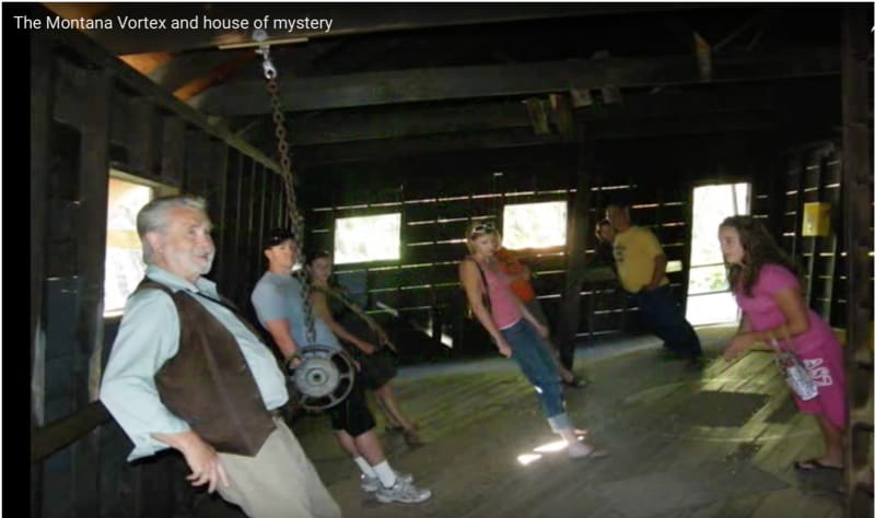 Visitors experience strange forces at the Montana House of Mystery. Why does the chain hang at a different angle from the angle at which the people stand?