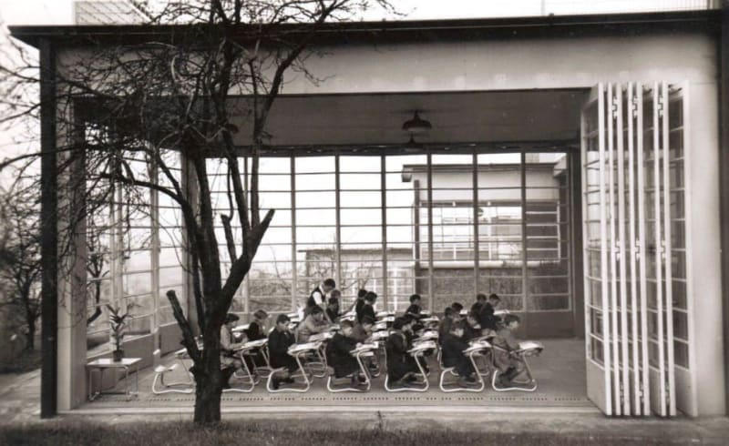 A classroom with its glass wall opened up at the open-air school in Suresnes, France, designed by Eugene Beaudoin and Marcel Lods, completed in 1935