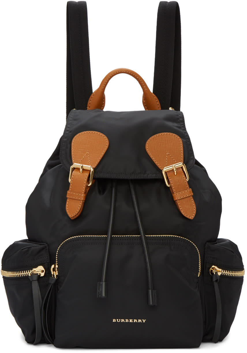 6ceb80fae25e Burberry Black Medium Rucksack  1250.00 Nylon backpack in black. Leather  accents in brown throughout. Carry handle at top. Chain accent at lightly  padded ...