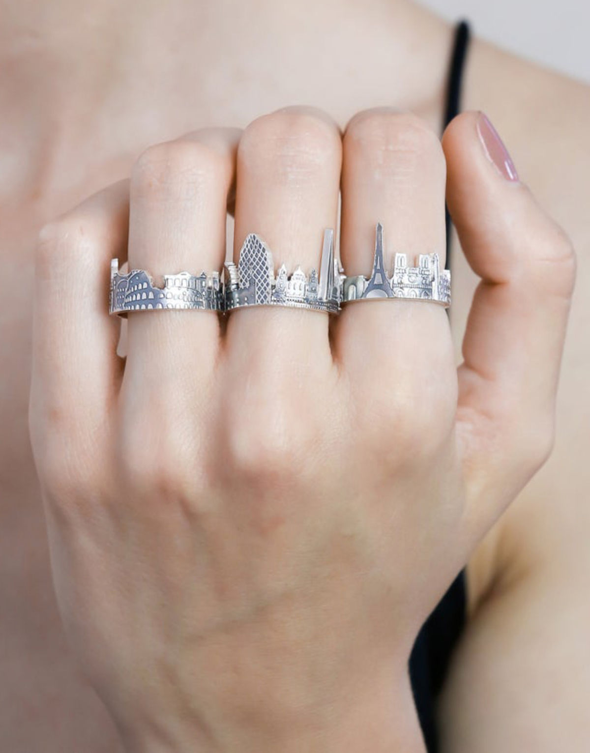 hand wearing silver rings in the shape of city skylines