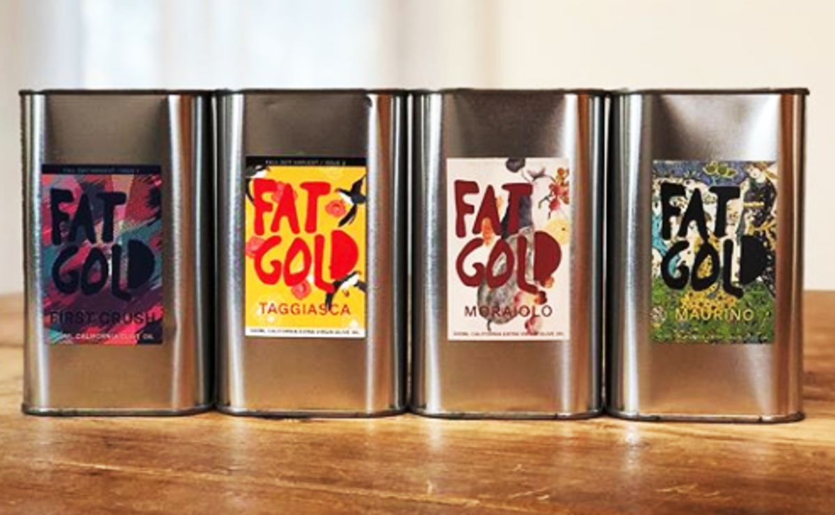 tin containers of olive oil with colorful labels