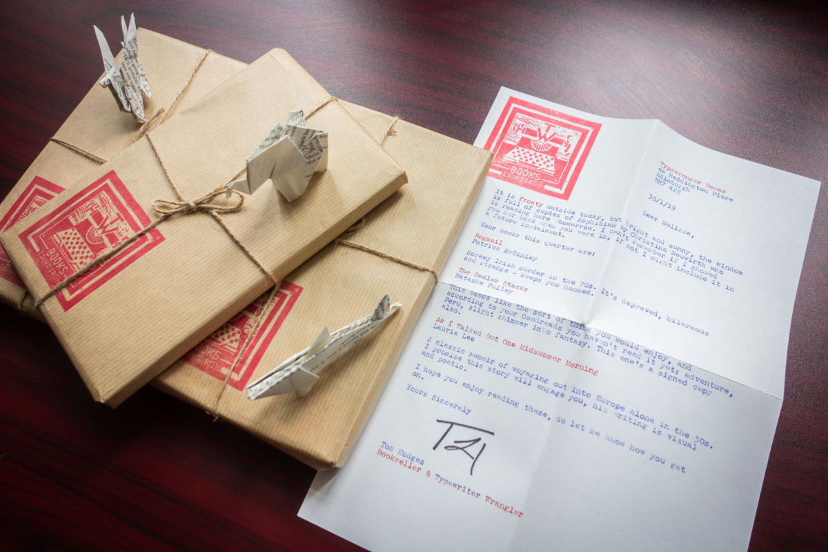 three books wrapped in brown paper