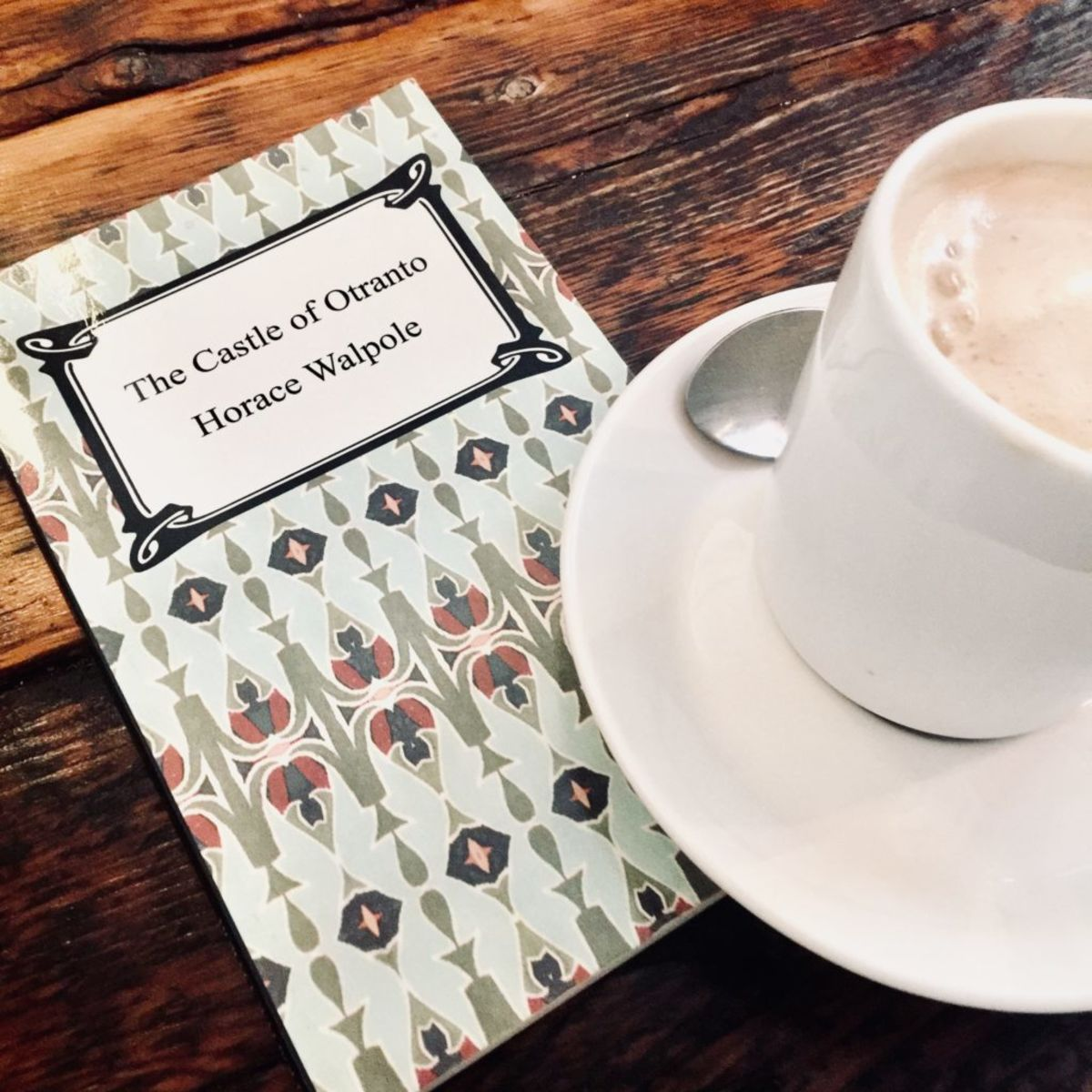 the book The Castle of Otranto with a cup of coffee