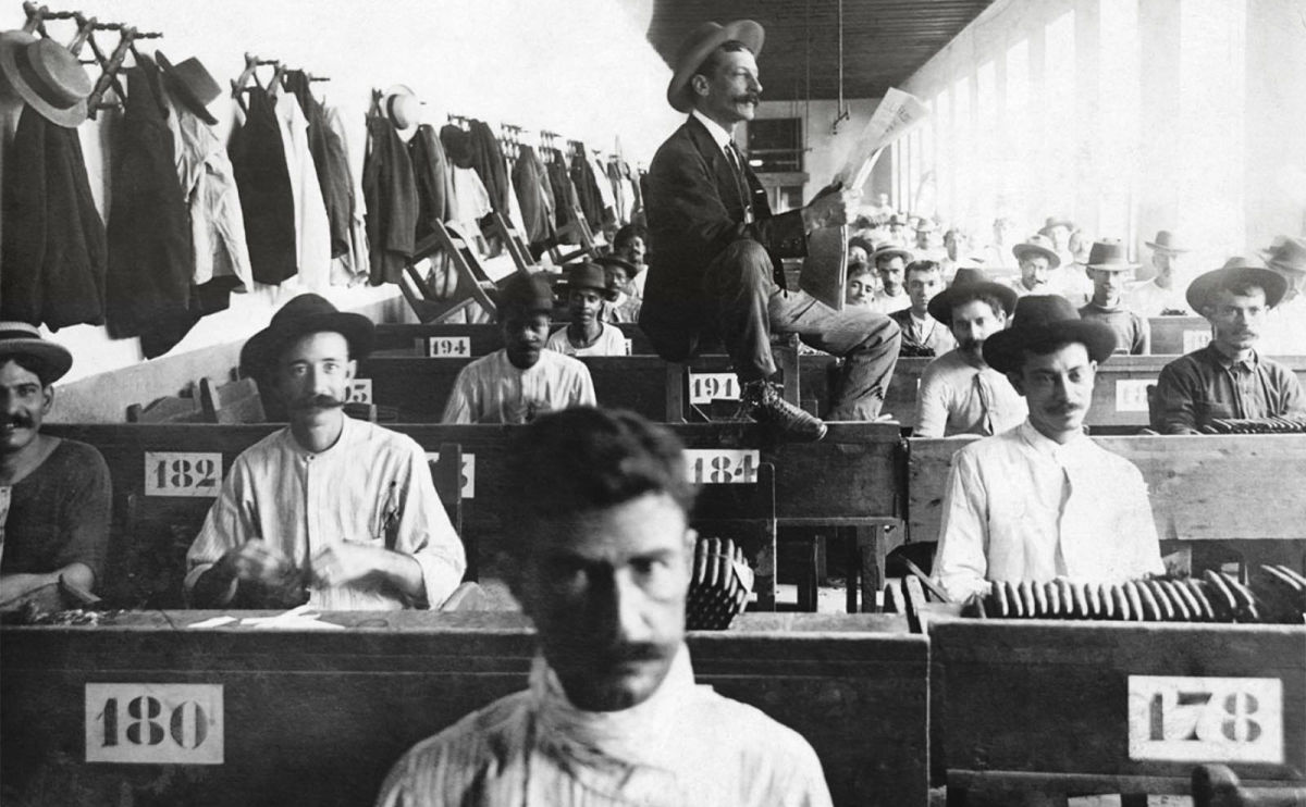 a gentleman reads to tobacco factory workers in cuba