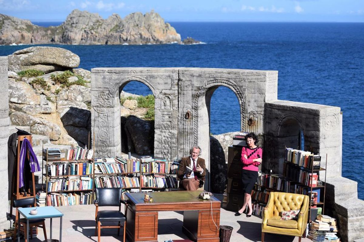 actors on a stage overlooking the ocean with bookshelves and easy chairs