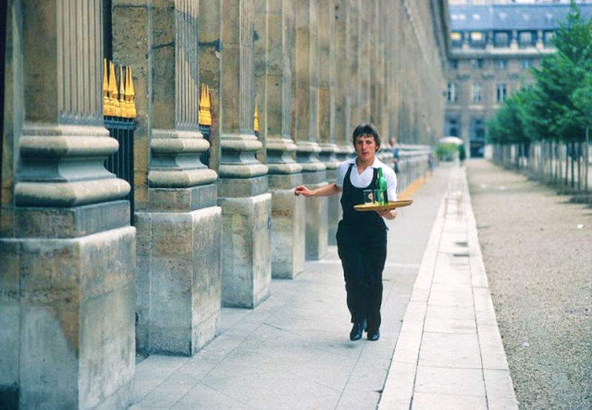 a waiter carries a serving tray down a street in paris