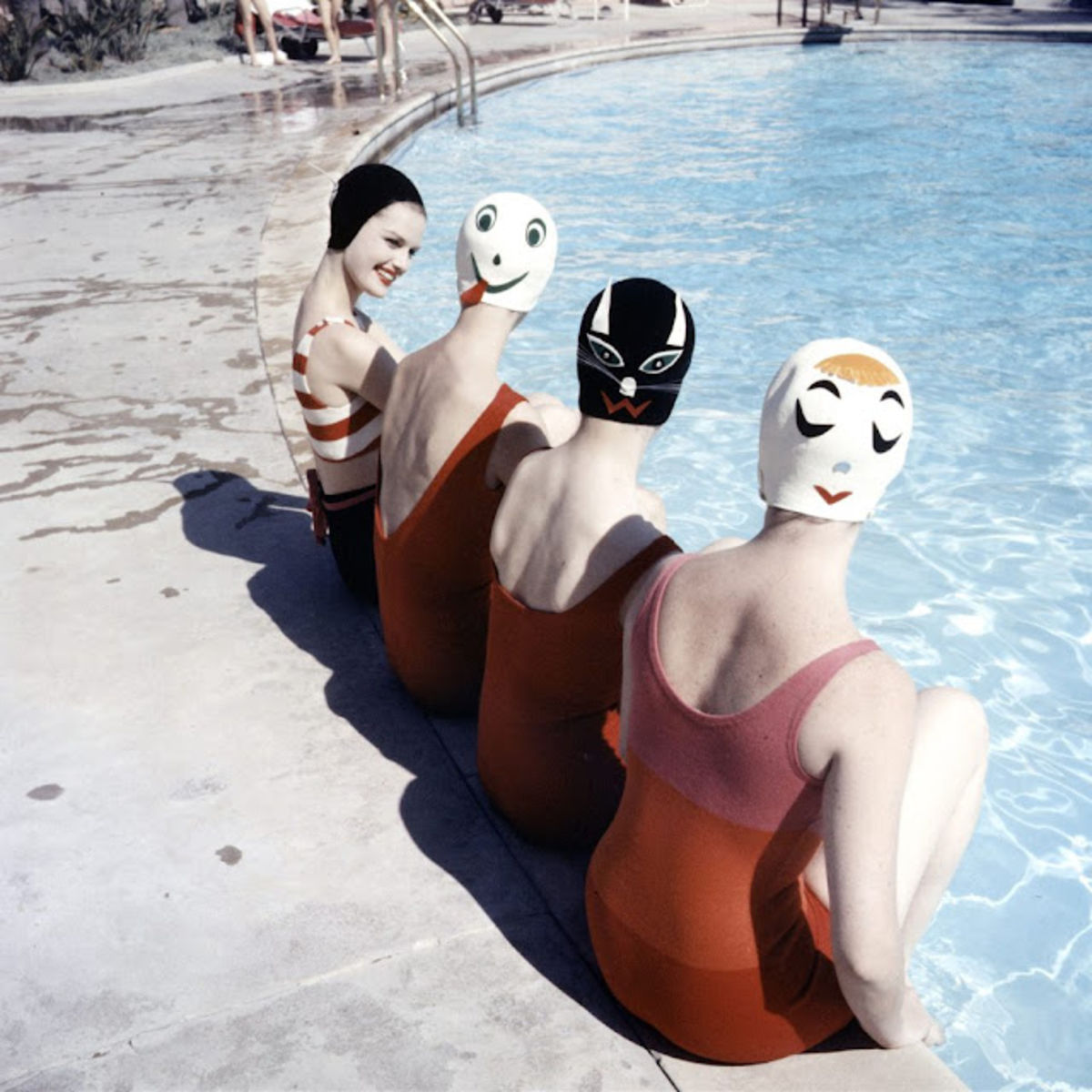 girls in bathing suits and vintage swimming caps printed with faces by a swimming pool