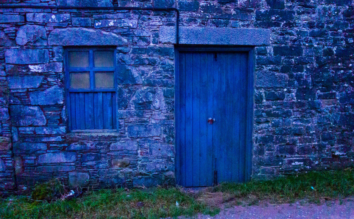 a blue wooden door set in a stone wall