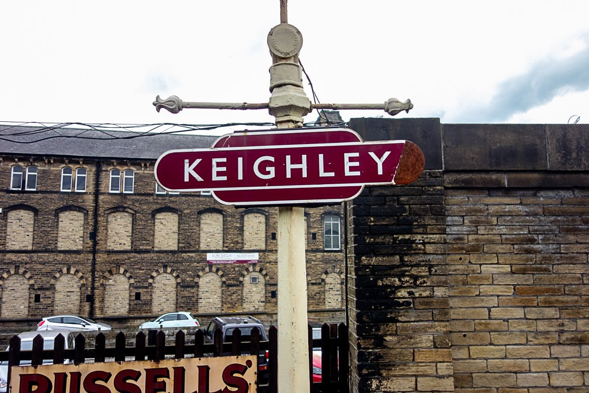 maroon sign with the word keighley at the keighley train station