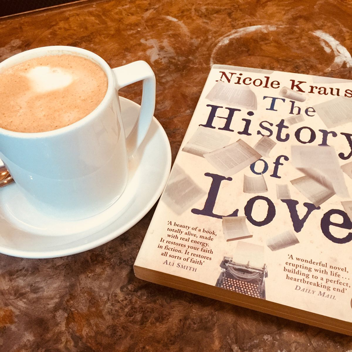 the book The History of Love with a cup of coffee