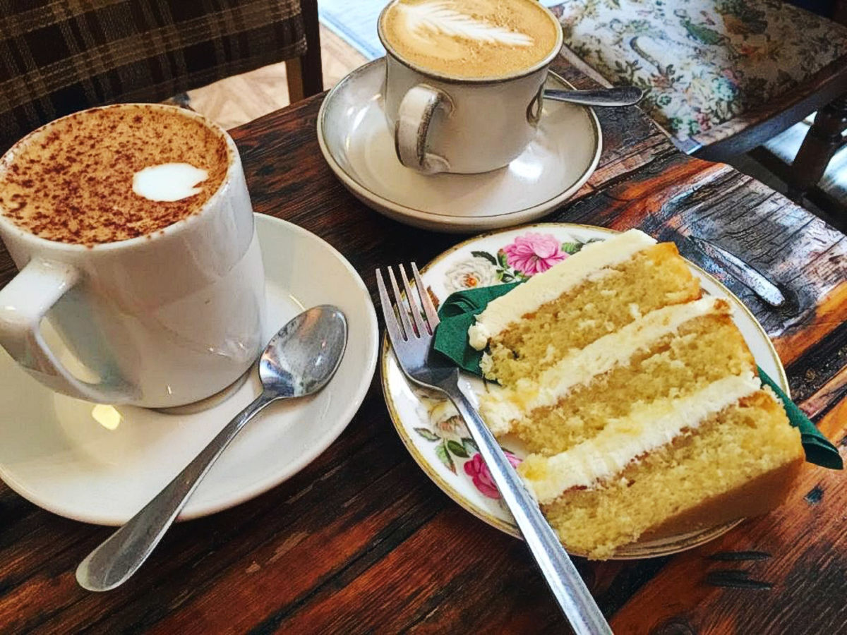 two cappuccinos with a large slice of layer cake