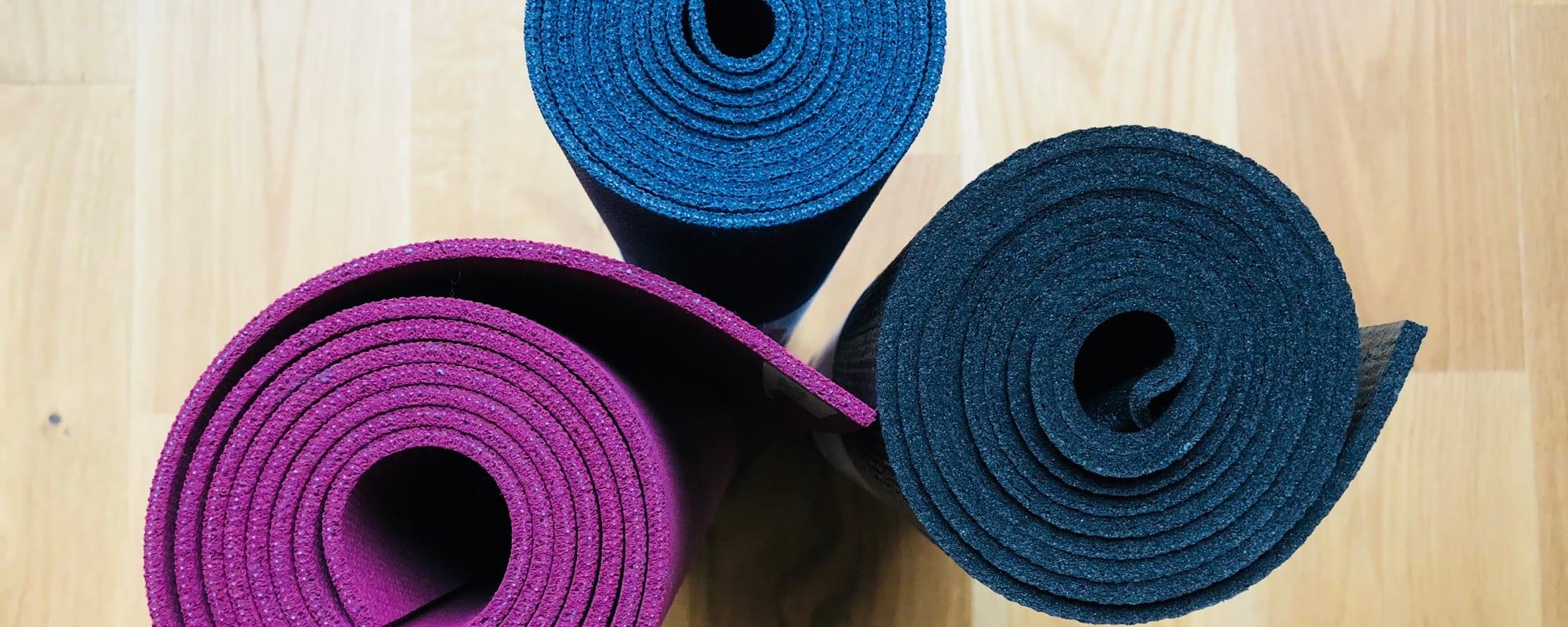 Tre yogamåtter i forskellige farver
