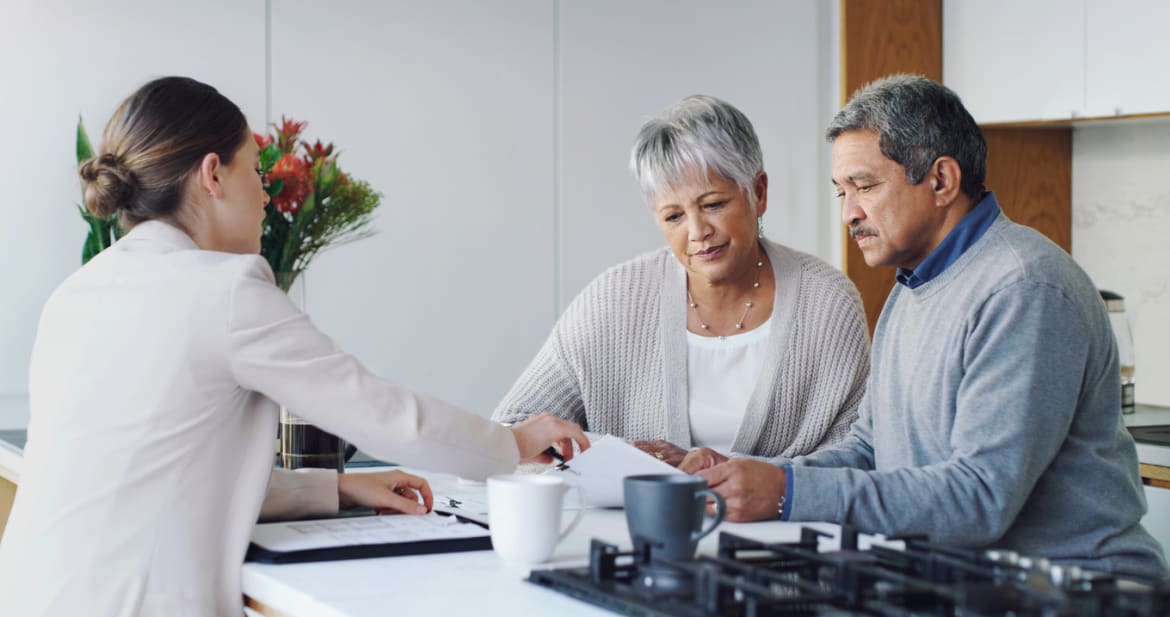 Shot of a senior couple meeting with an agent to discuss paperwork at home
