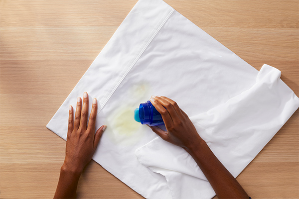 a person is treating white cloth with Tide detergent