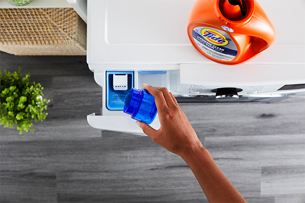 A person pouring Tide liquid detergent into the detergent drawer