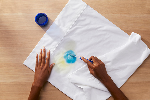 A person using a toothbrush to pretreat a stain with Tide liquid detergent on a white shirt