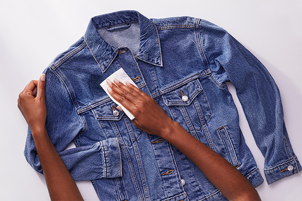 A person wiping off excess from denim jacket