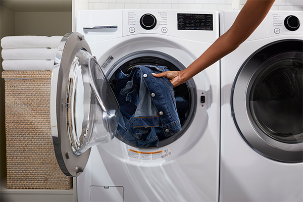 A person is loading denim garments into the washing machine drum