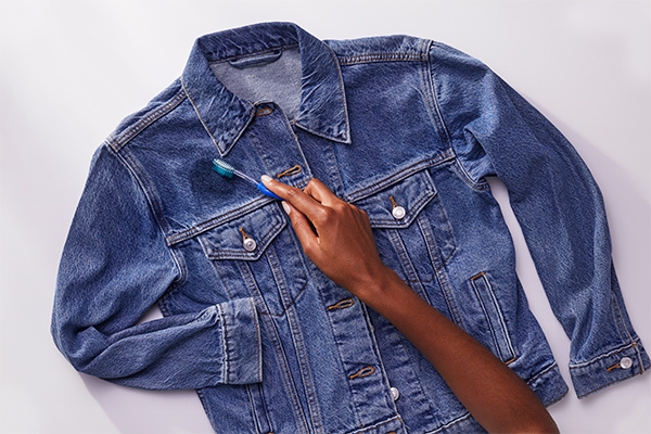 A person brushing off excess from denim jacket