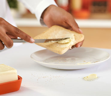A person spreading butter on a slice of toast