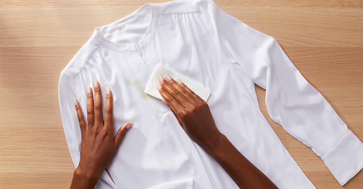A person removing excess stain from a white shirt with a toothbrush with a paper towel