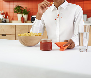 A person wearing a white shirt stained with salsa sauce