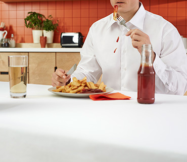 A person wearing a white shirt stained with ketchup