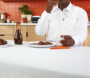 A person wearing a white shirt stained with BBQ Sauce