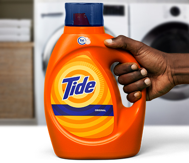 A person holding a Tide liquid detergent product in front of a washer