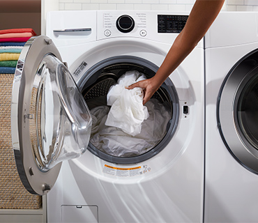 A person loading white clothes into the washing machine drum