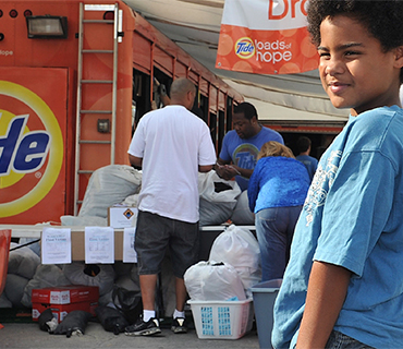 A child getting his clothes cleaned at a Tide Loads of Hope truck