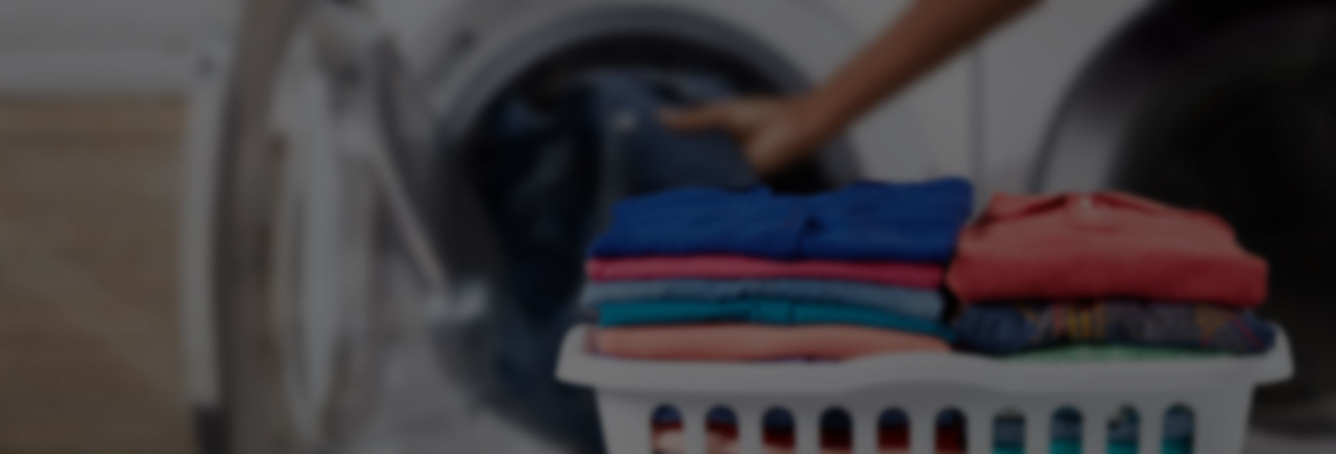 A person loading clothes into a washing machine