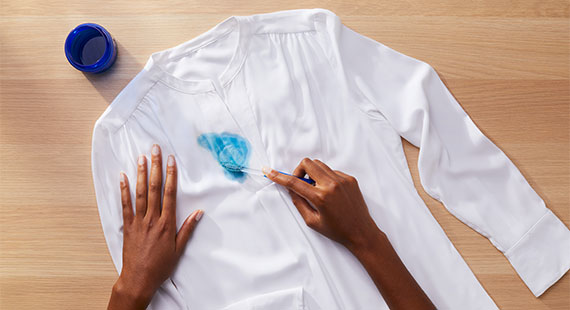 A person preteating a stain on a whit shirt with Tide liquid detergent and a toothbrush