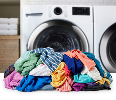 A pile of colorful garments in front of a washer