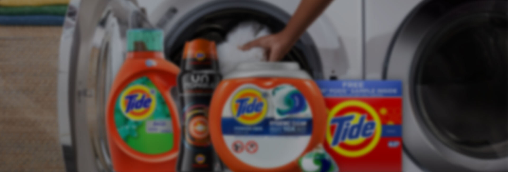 Various Tide products in front of a washer