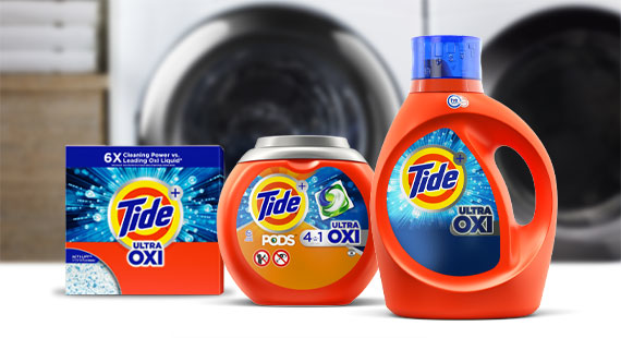 Tide powder, PODS and liquid products in front of a washer