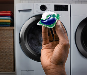 A person holding a Tide PODS product